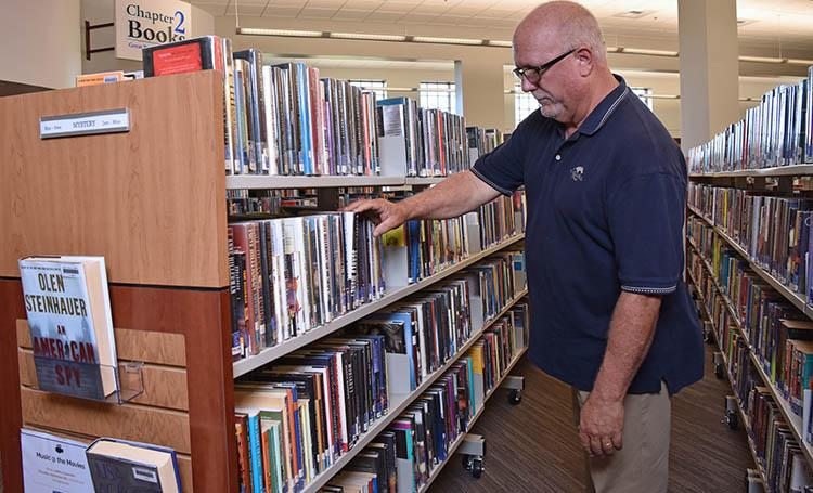 library patron-man looking at books