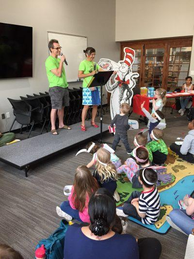 2 adults in green shirts perform to an audience of children and families next to a Dr. Seuss cutout
