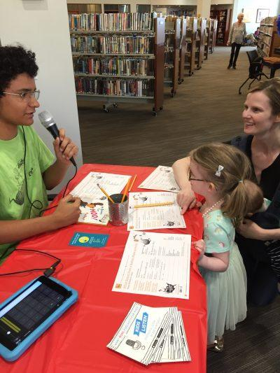 A man holding a microphone speaks to a child and parent at a table covered in papers
