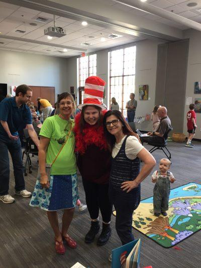 A woman in a green shirt, a woman in a Cat in the Hat hat, and a representative from First Things First non-profit pose for a photo
