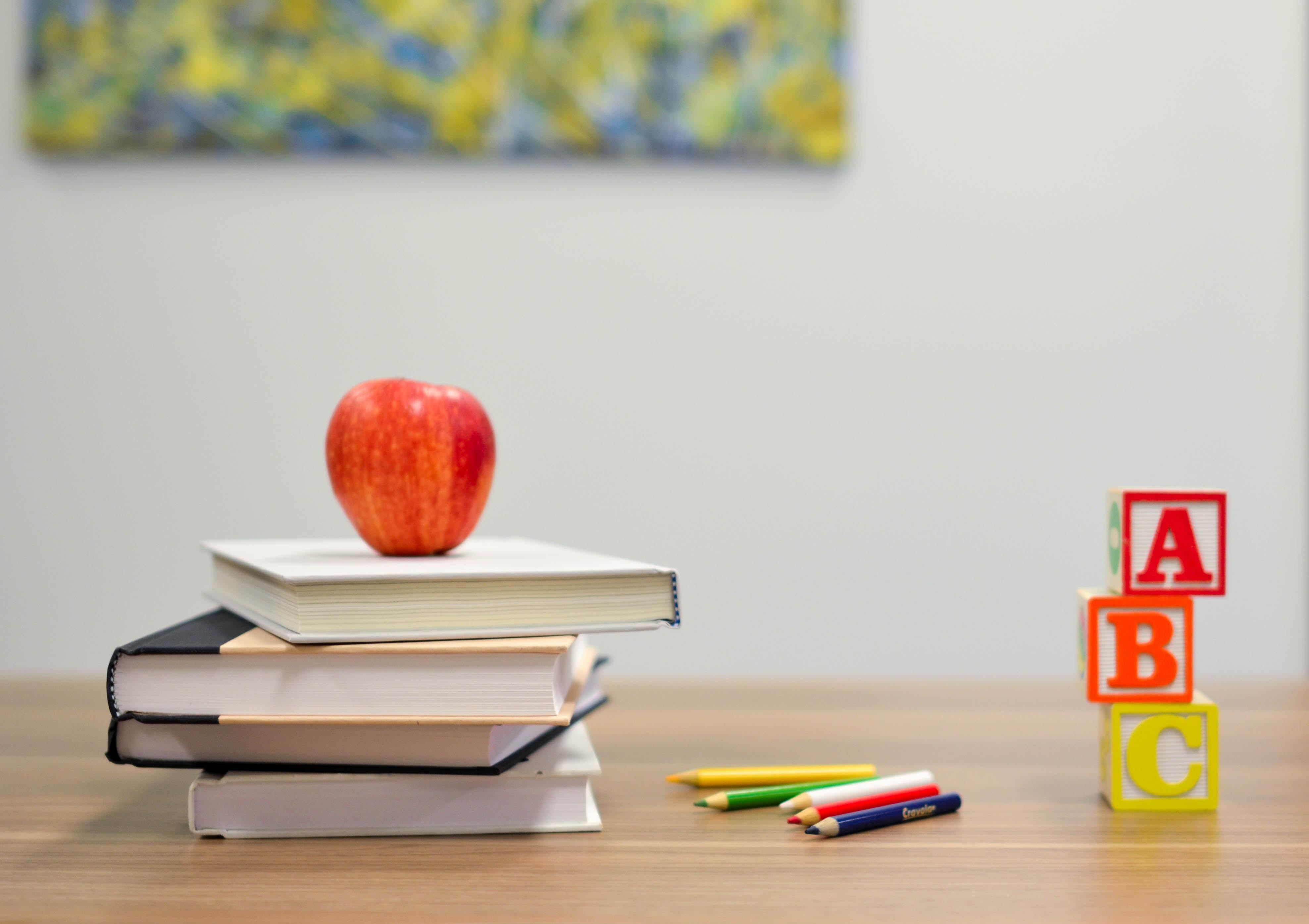 an apple sits on top of a stack of books next to a pile of colored pencils and ABC blocks
