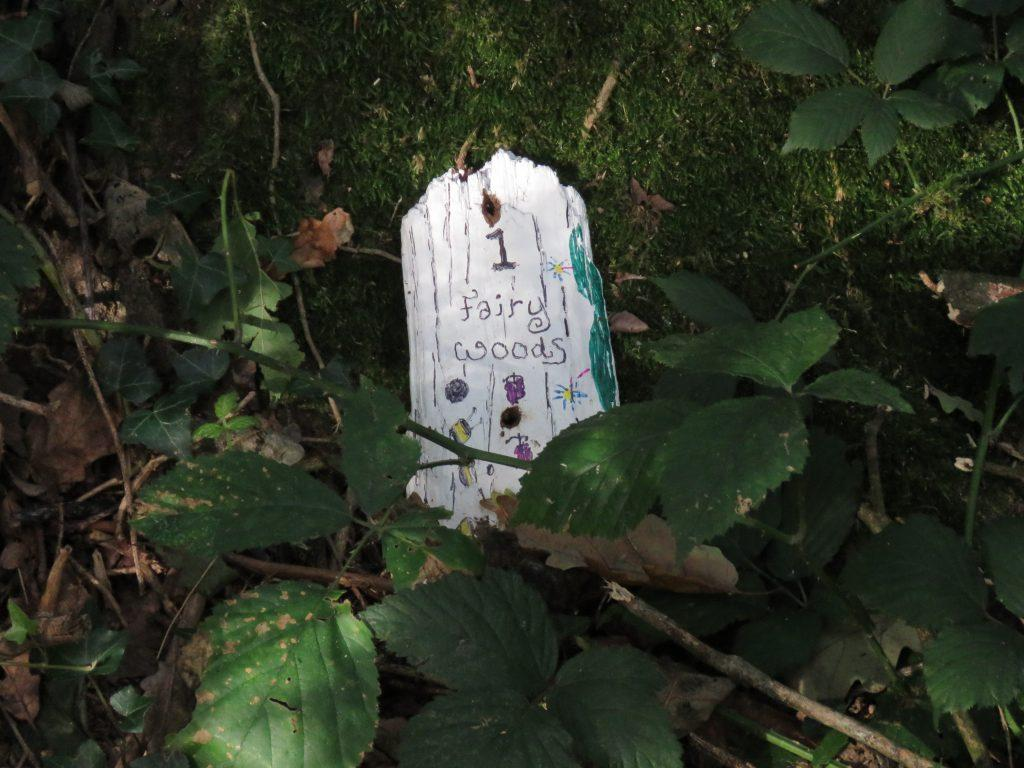 A white fairy door reads 1 Fairy Woods in a green forest