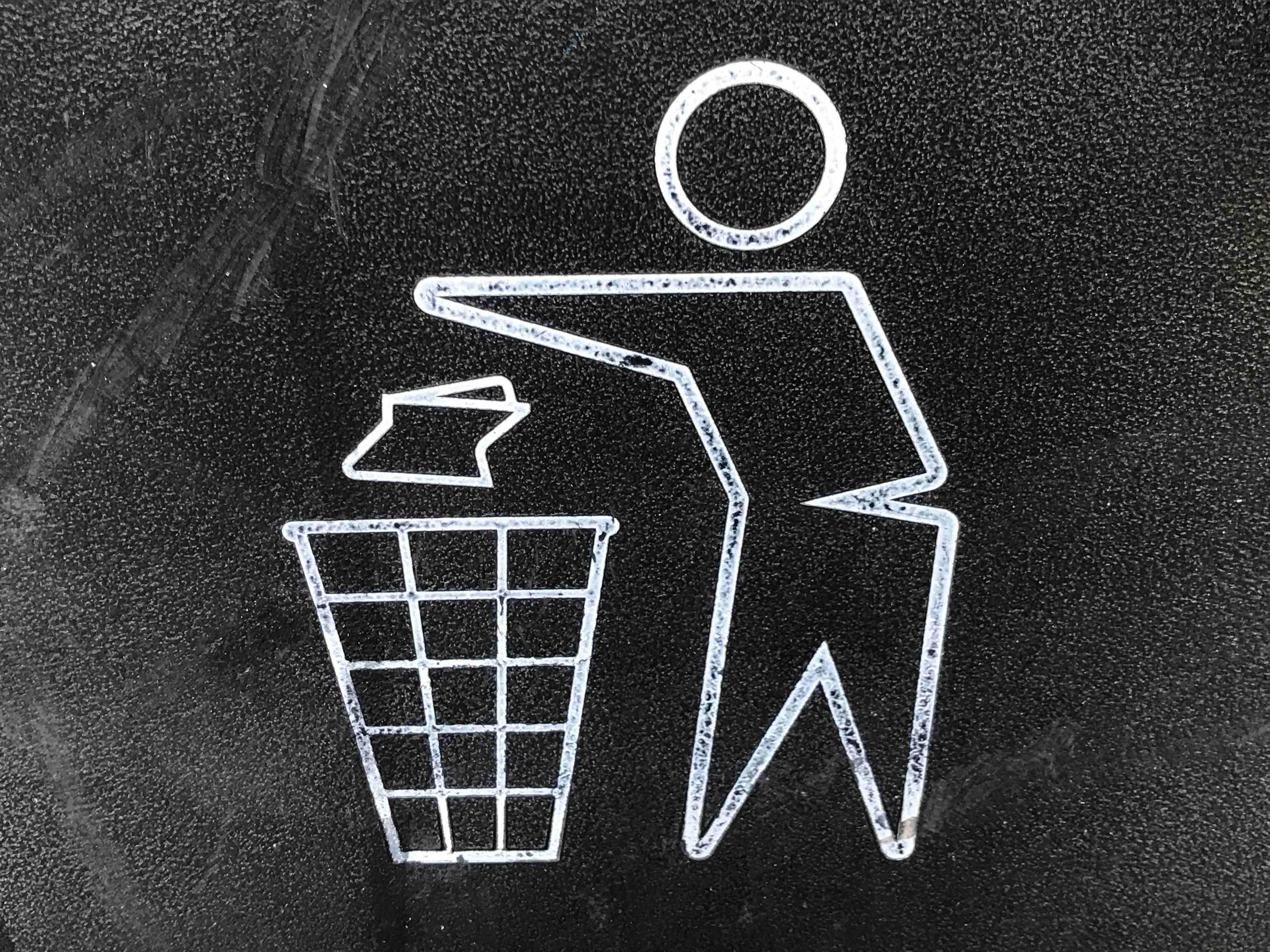 Chalk drawing of person disposing waste into trash bin