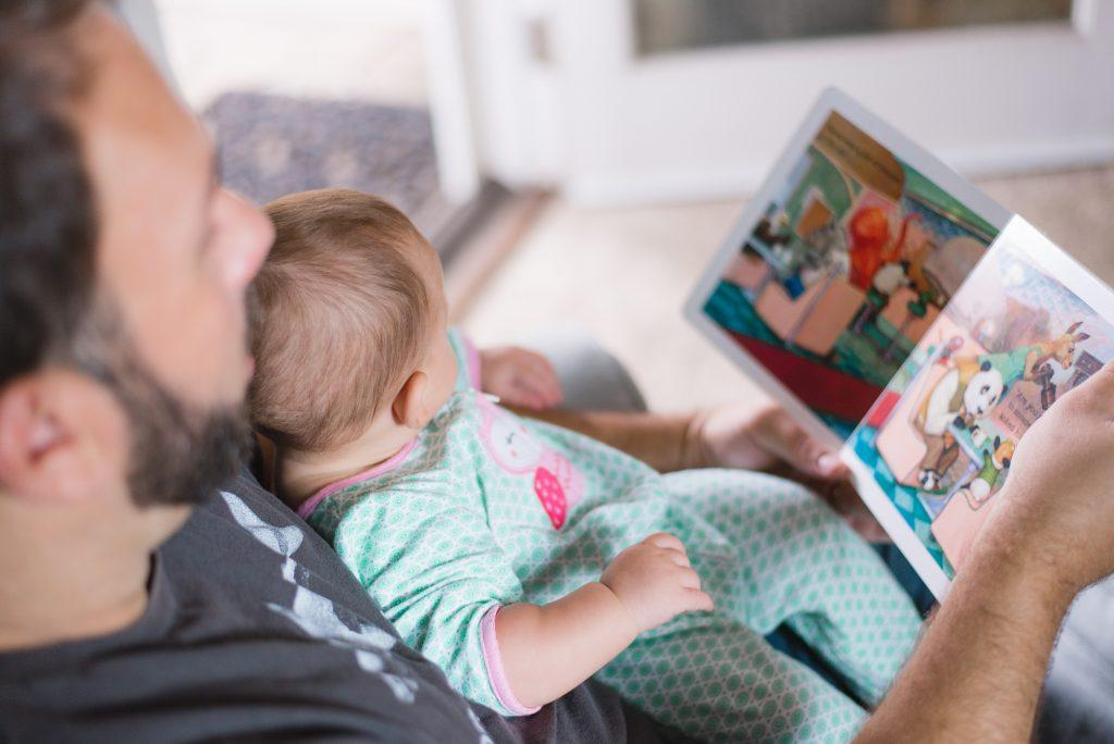 a male adult holds a baby on a lap while reading the baby a story