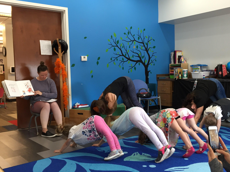 several kids do downward dog yoga pose during storytime