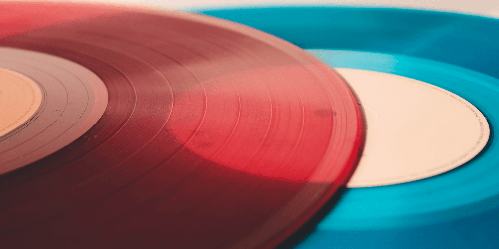 a close up photo of a red vinyl record sitting on top of a blue vinyl record